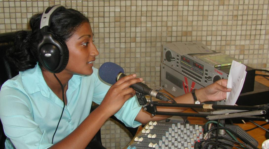 En tjej pratar i radio under hennes praktik på en radiostation utomlands.